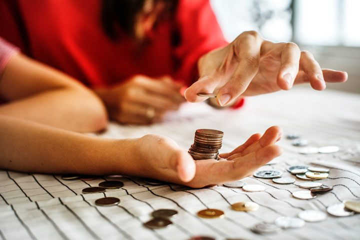 woman stacking pennies in palm of guy's hand