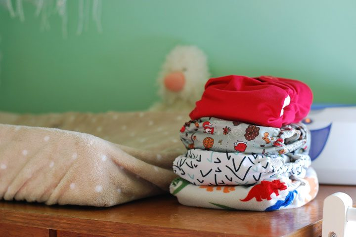 stack of cloth diapers - save money on cloth vs disposable diapers