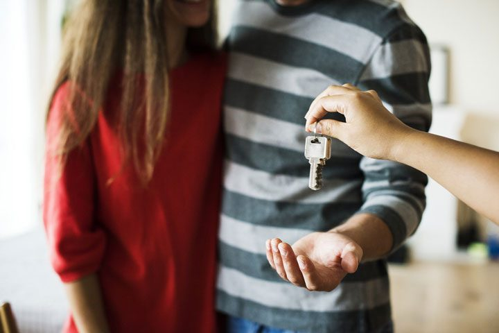 living with parents to save money - keys handed to young millennial couple