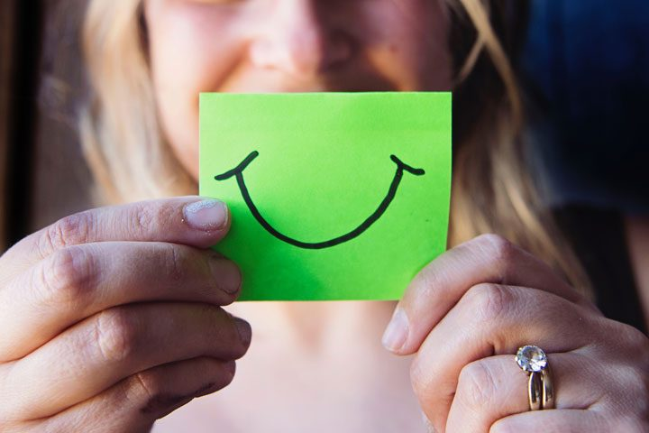 woman holding post it with smiley face in front of face