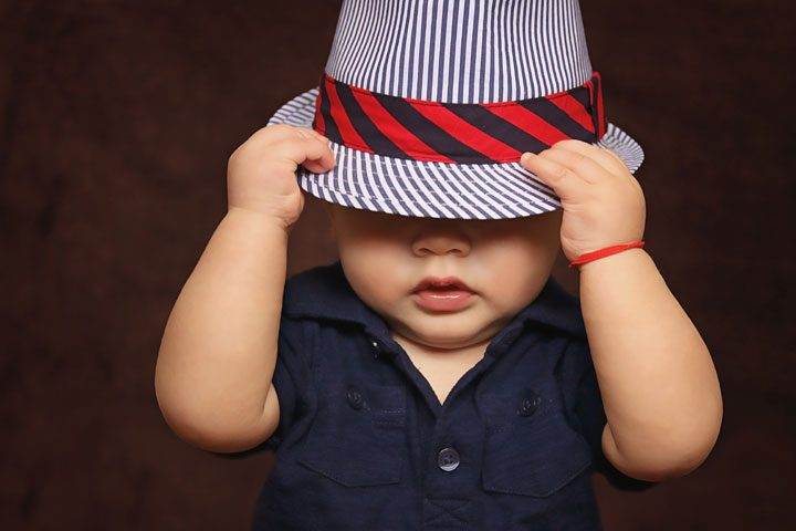 baby in blue polo and striped hat over eyes